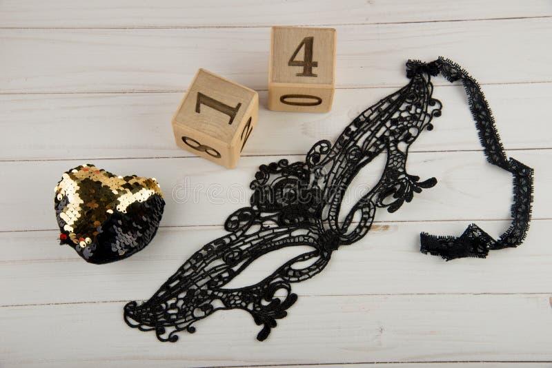 在木立方体的顶视图与第1,4金黄心脏和黑鞋带面具 免版税库存照片