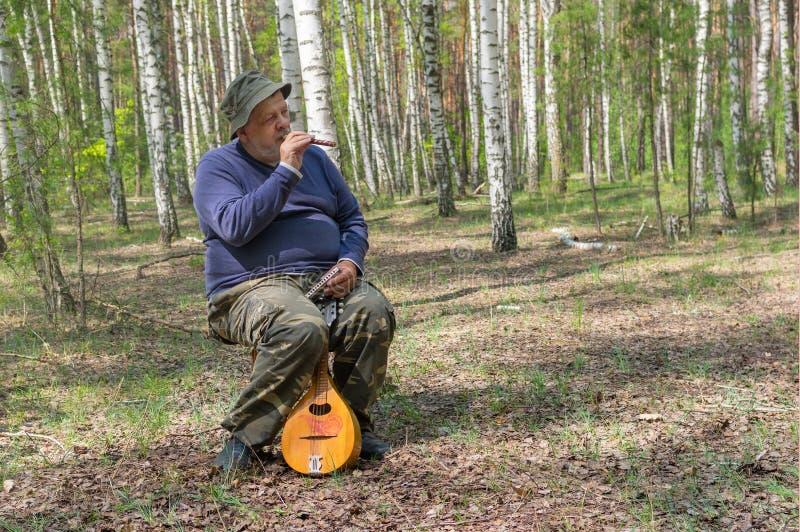 在木管乐器sopilka的资深使用的音乐,当坐凳子时 免版税图库摄影