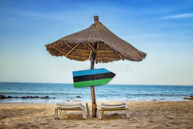 在木箭头标志的桑给巴尔旗子 有两个太阳懒人和一把阳伞在海滩 这是热带的 免版税库存照片