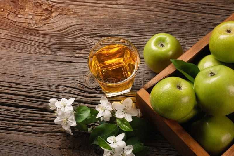 在木箱的成熟绿色苹果有白花和杯分支的在一张木桌上的新鲜的汁液 免版税库存照片