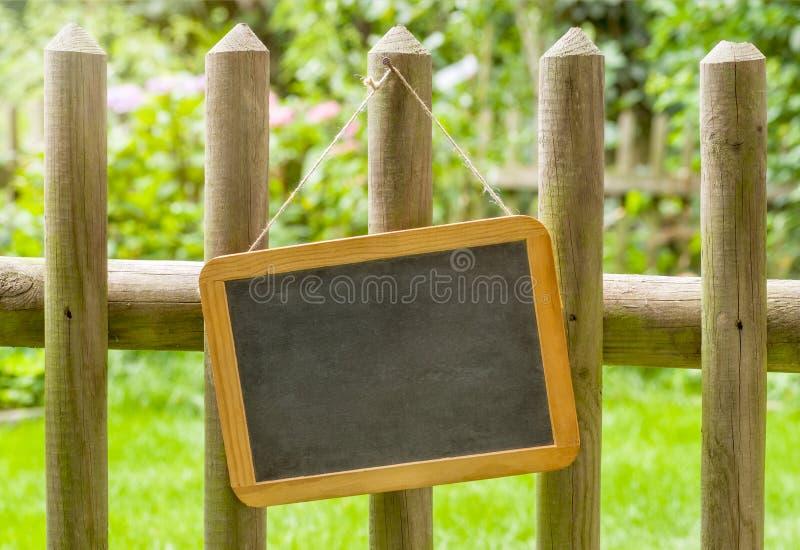 在木篱芭的一个空的黑板 免版税库存图片