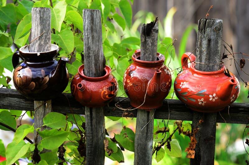 在木篱芭的四个陶瓷茶壶 免版税库存图片