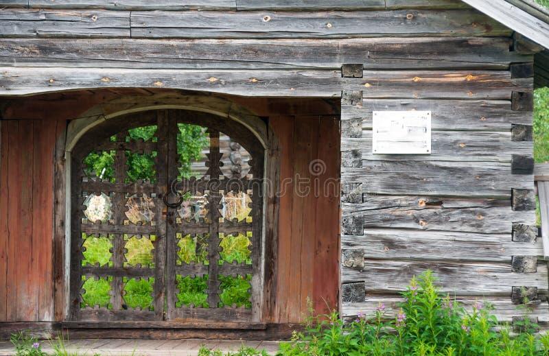 在木篱芭的老木被雕刻的门 免版税库存图片