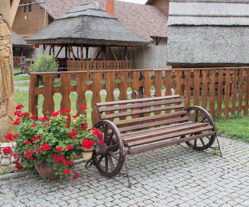 在木篱芭种族房子附近的装饰长凳做从 免版税库存照片