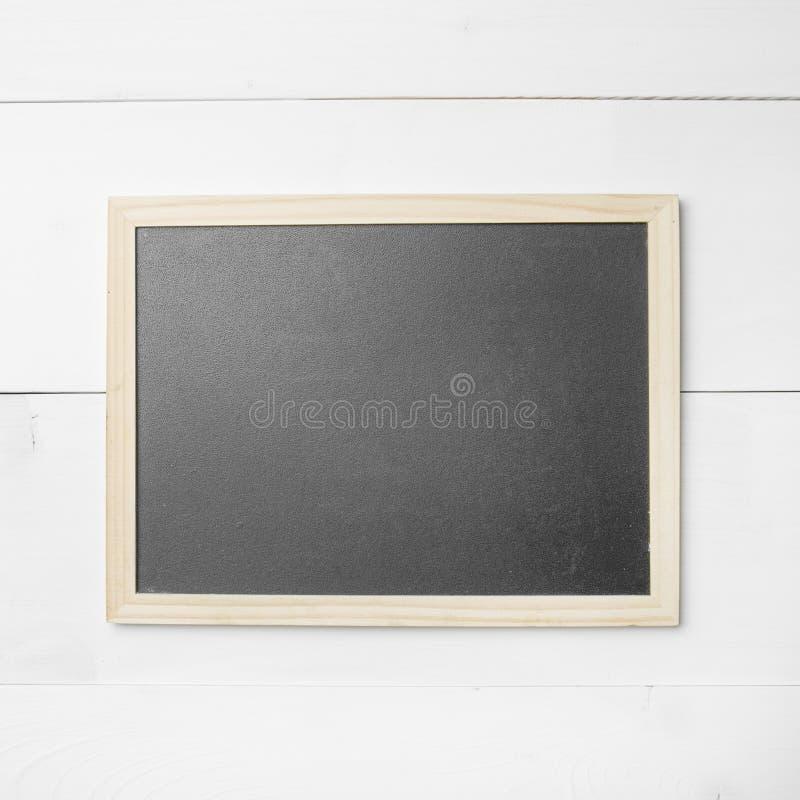 在木纹理的小空的黑板 免版税库存图片