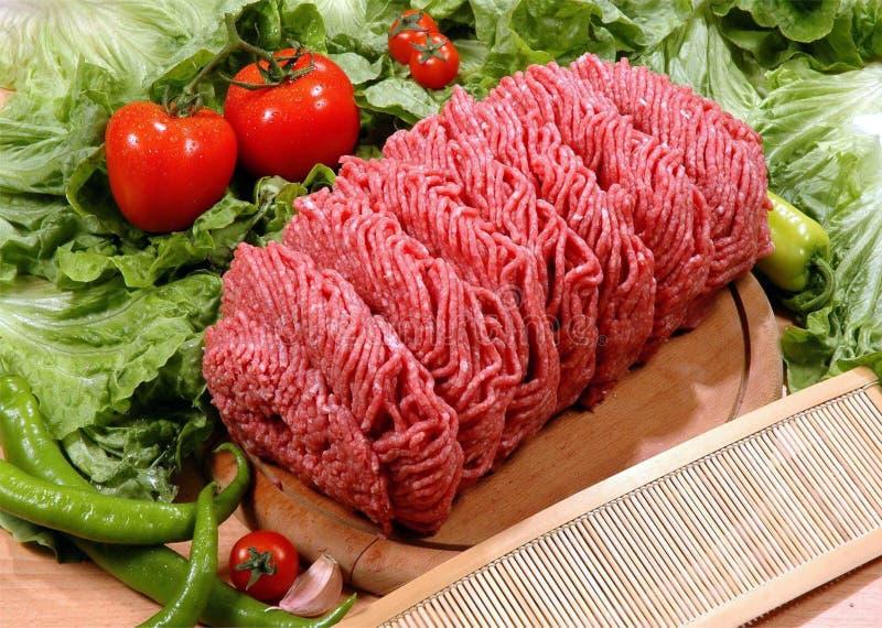 在木绞细牛肉,蕃茄,胡椒,绿色的切板 免版税库存图片
