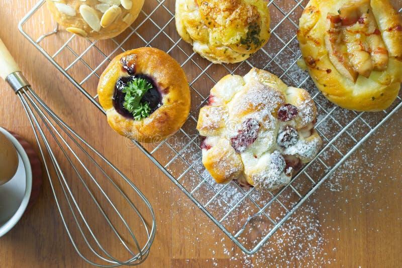 在木背景、被分类的面包和酥皮点心,不同的种类的新近地被烘烤的丹麦酥皮点心小圆面包 免版税图库摄影