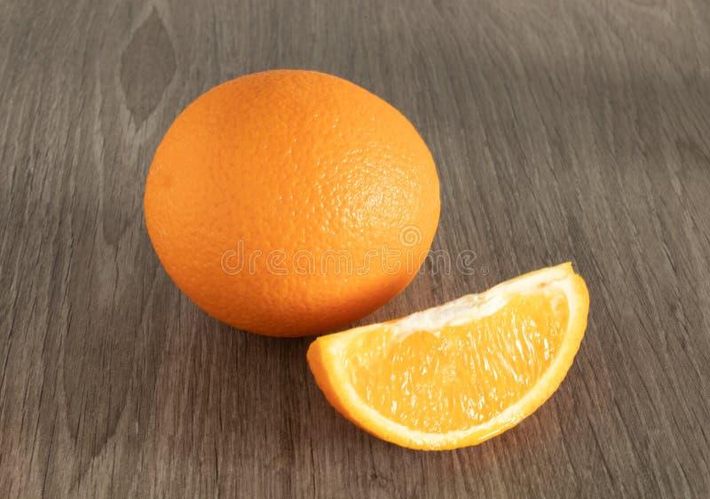 在木背景关闭的整个橙色下个切片 库存照片