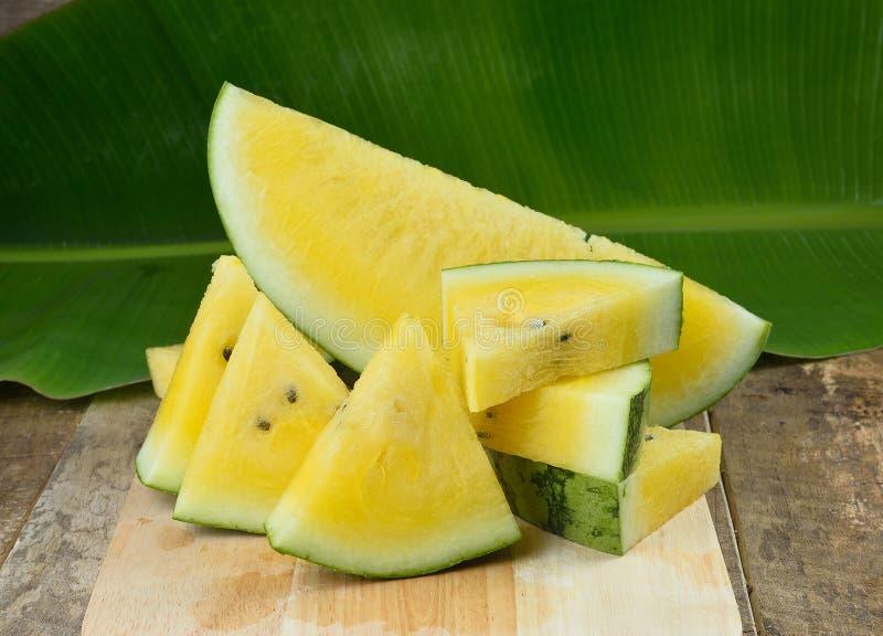 在木背景切的黄色西瓜 免版税库存照片