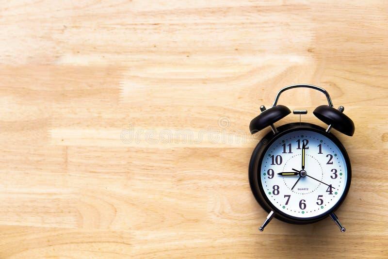 在木背景放映时间概念的黑闹钟 库存图片