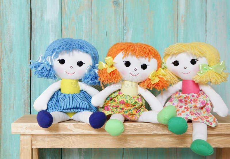在木背景的三个愉快的布洋娃娃 图库摄影