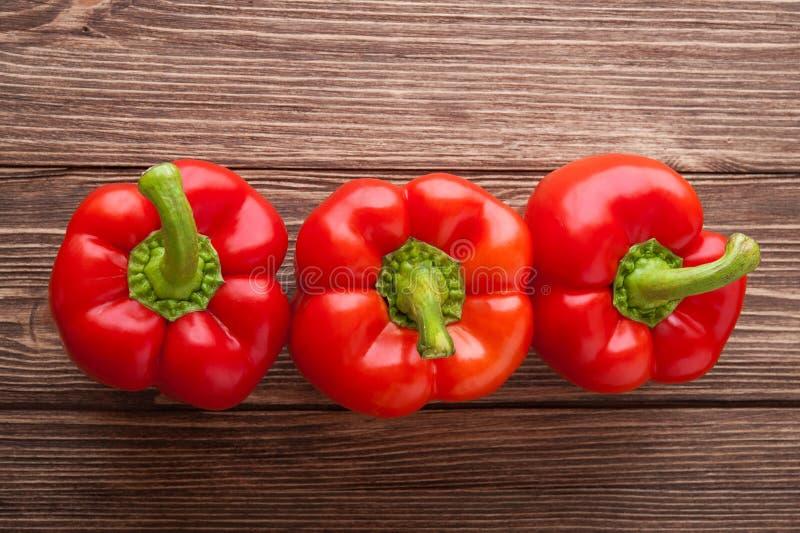 在木背景的三个红色甜椒 顶视图 库存照片