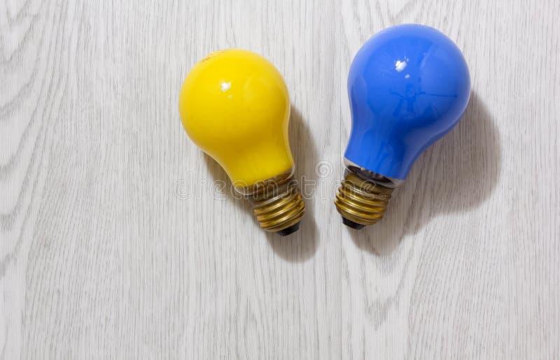 在木背景的两个色的电灯泡 免版税库存图片