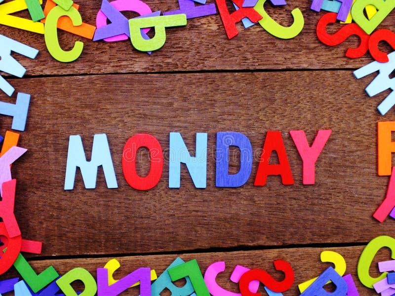 在木背景的五颜六色的木字母表星期一拼写 免版税库存照片