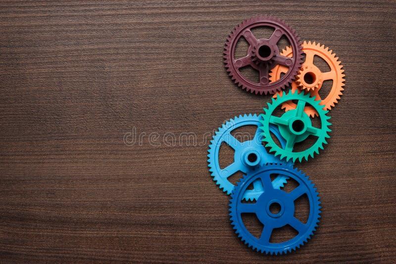 在木背景的五颜六色的齿轮 库存照片
