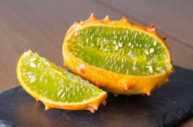 在木背景的切的果子Kivano瓜 关闭 免版税图库摄影