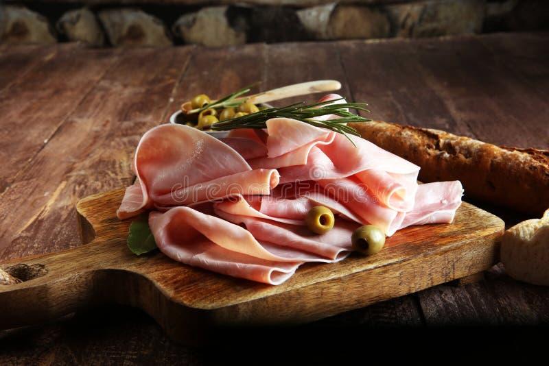 在木背景的切的火腿 新鲜的prosciutto slic猪肉的火腿 免版税库存图片