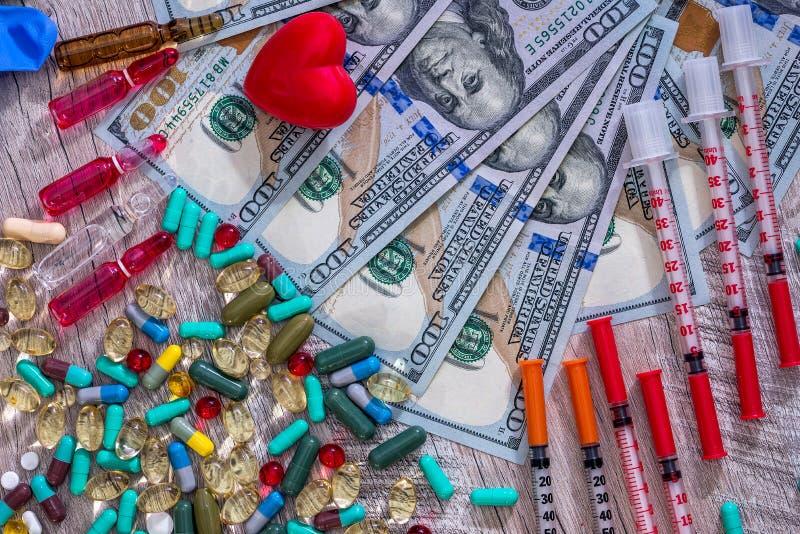 在木背景的医疗构想与美元、片剂和注射器 免版税库存图片