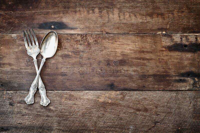 在木背景的古色古香的银器 免版税库存图片