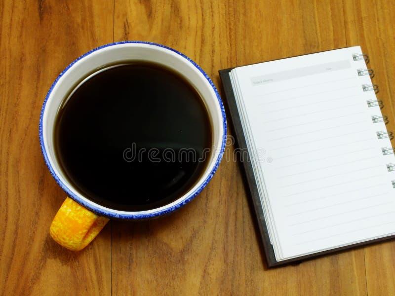 在木背景的咖啡和纸笔记本 库存照片