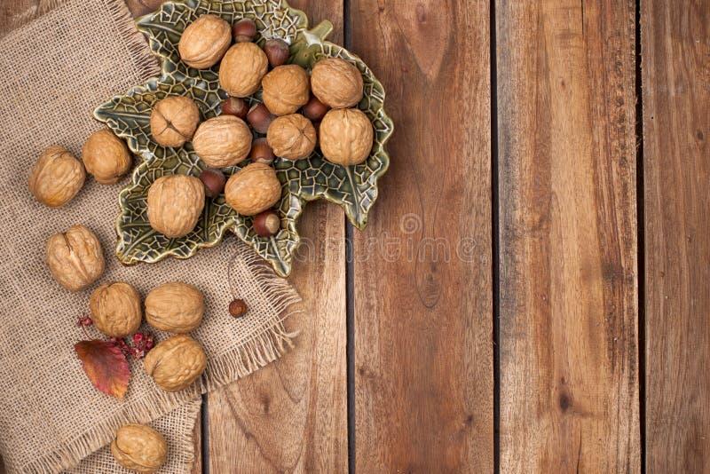 在木背景的坚果 秋天装饰和食物 抽象背景同类的照片结构葡萄酒 免版税库存照片