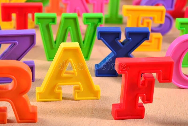 在木背景的塑料五颜六色的字母表信件 免版税库存照片