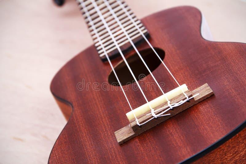 在木背景的尤克里里琴吉他 库存照片