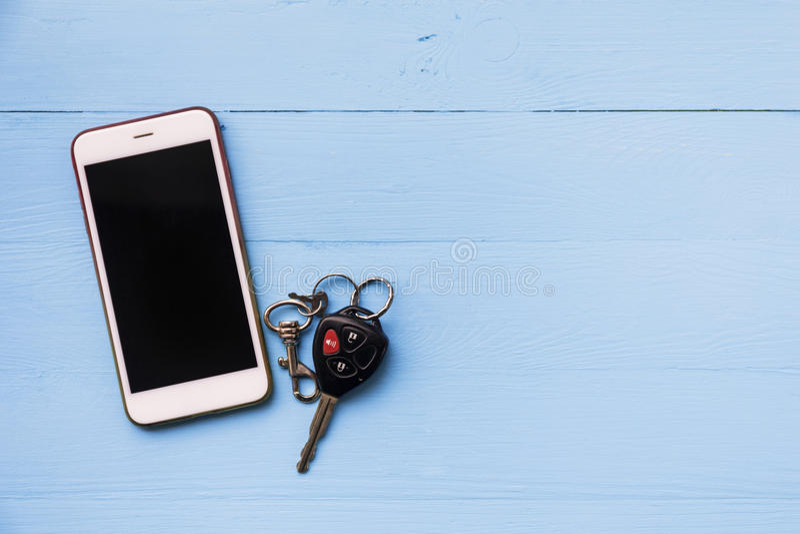 在木背景的手机和汽车遥远的钥匙 免版税图库摄影