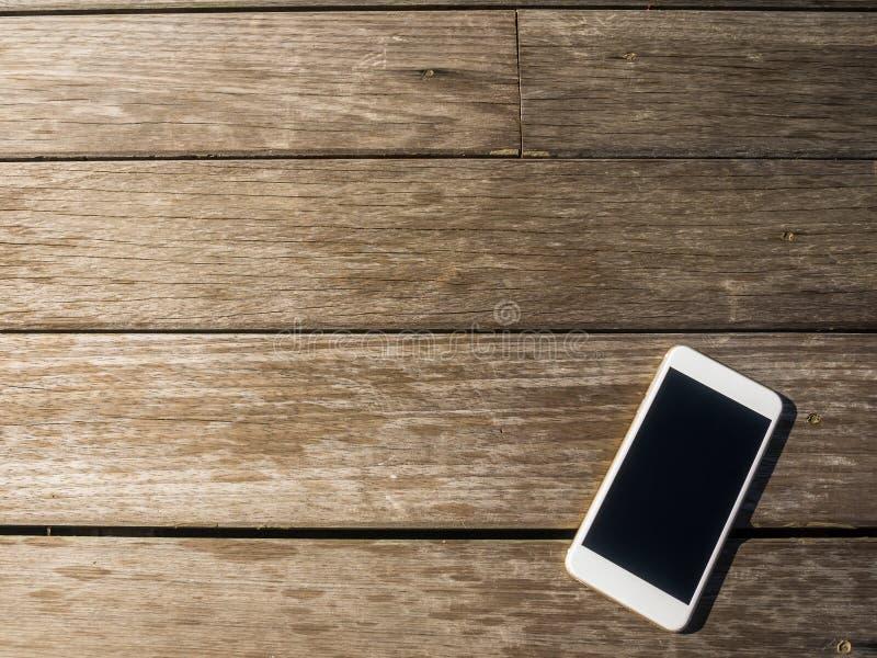在木背景的手机 免版税图库摄影