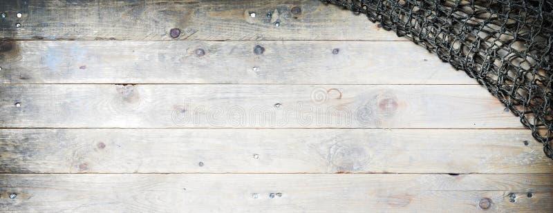 在木背景的捕鱼网静物画 免版税库存照片