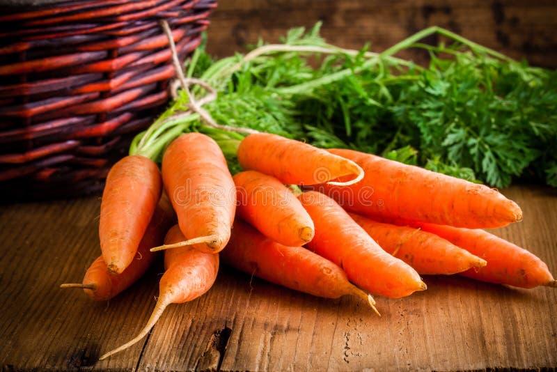 在木背景的新鲜的有机红萝卜 免版税图库摄影