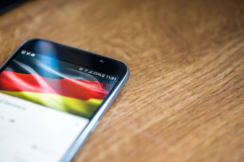 在木背景的智能手机与5G网络标志25%充电和德国旗子在屏幕上 库存图片
