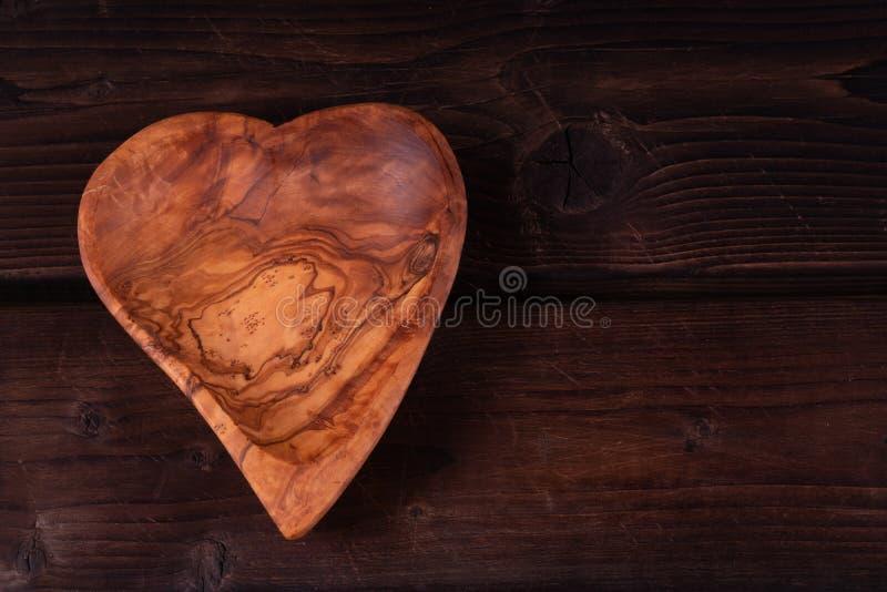 在木背景的板材心形,低调,手工制造,土气 免版税库存照片