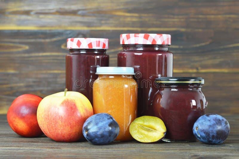 在木背景的果酱瓶子 免版税库存图片