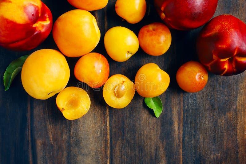 在木背景的核果 黄色李子、杏子和油桃 库存图片