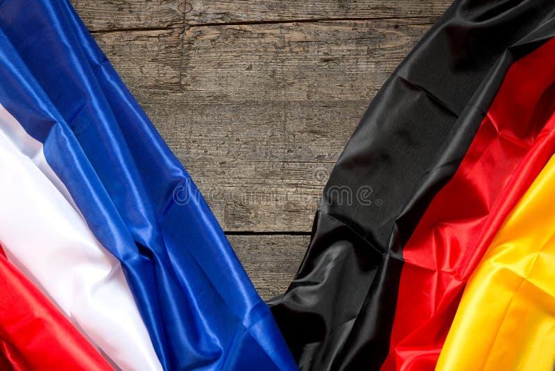 在木背景的法国和德国旗子 库存照片