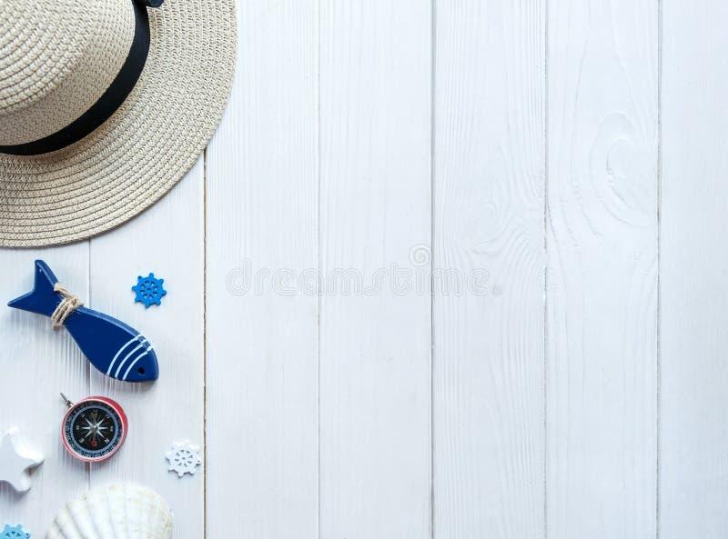 在木背景的海洋项目 海对象:草帽,泳装,鱼,壳 平的位置,拷贝空间 假期和旅行 免版税库存图片