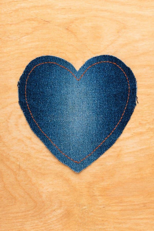 在木背景的牛仔裤心脏 图库摄影