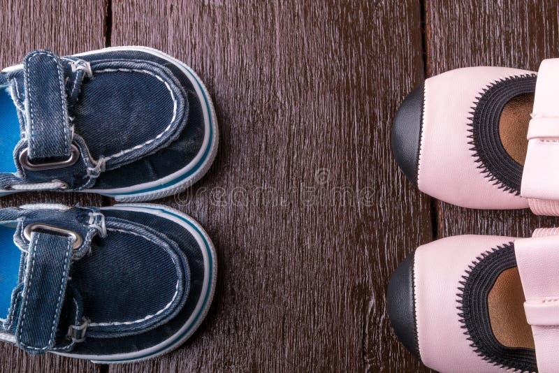 在木背景的男婴和女孩鞋子 儿童鞋类 顶视图 免版税库存照片
