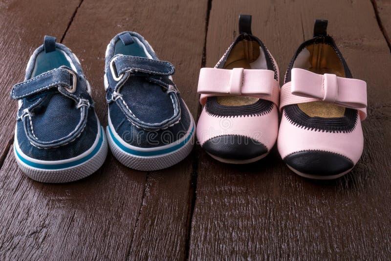 在木背景的男婴和女孩鞋子 儿童鞋类 图库摄影