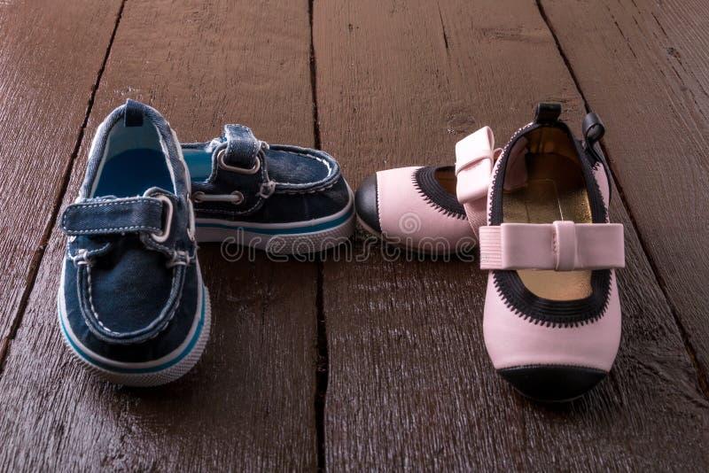 在木背景的男婴和女孩鞋子 儿童鞋类 免版税库存照片