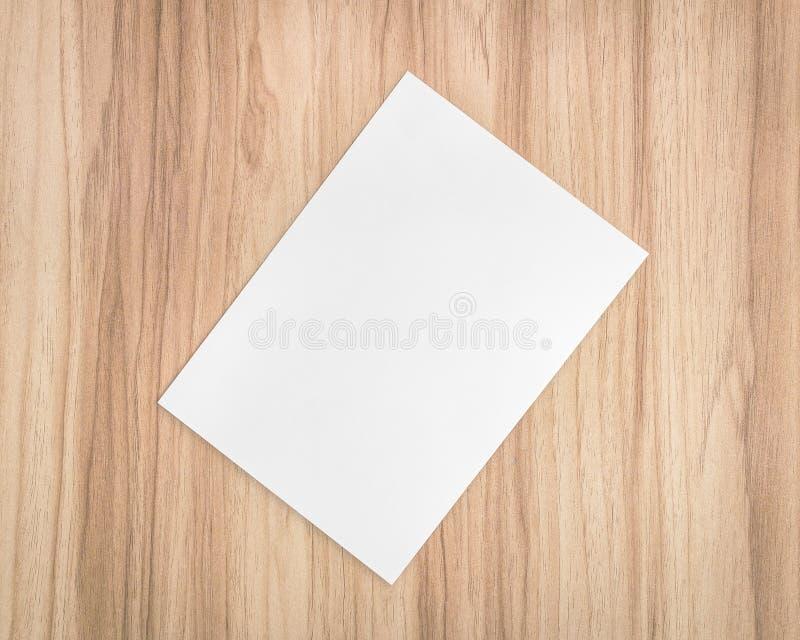 在木背景的白皮书板料 A4文件和空白模板文本的 免版税图库摄影