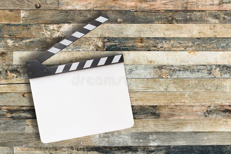 在木背景的白色电影拍板 免版税库存图片