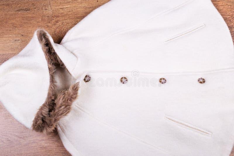 在木背景的白色羊毛雨披 免版税库存图片