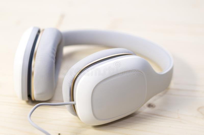 在木背景的白色耳机 免版税库存照片