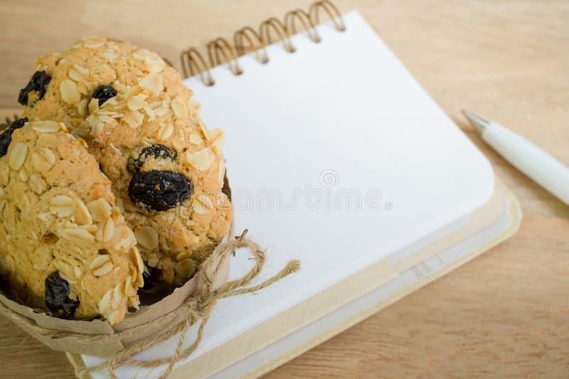 在木背景的空白的笔记本和燕麦曲奇饼 库存图片