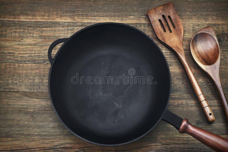 在木背景的空的干净的生铁煎锅 库存照片