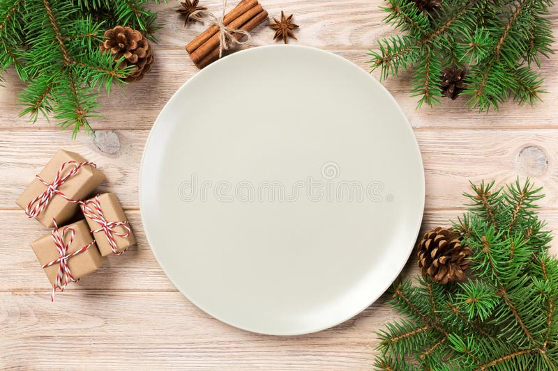 在木背景的空的白色表面无光泽的板材与圣诞装饰,圆的盘 概念新年度 免版税库存图片
