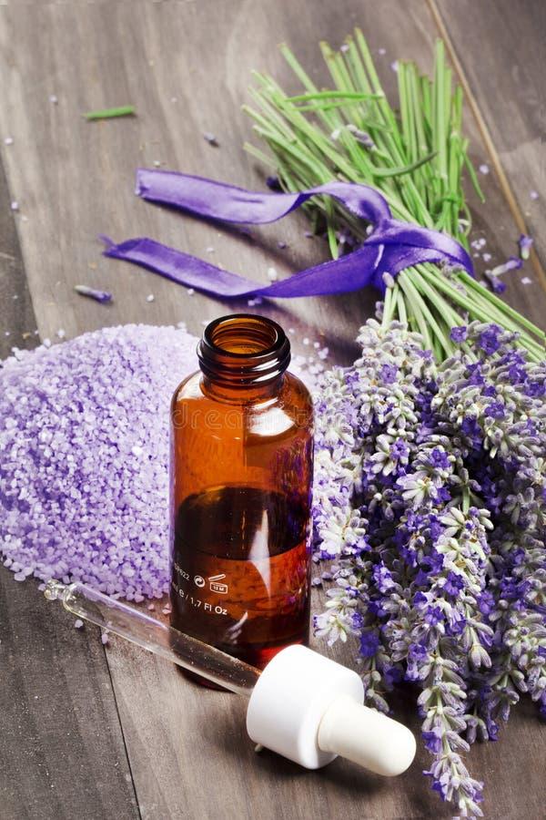 在木背景的精油和淡紫色花 免版税库存照片