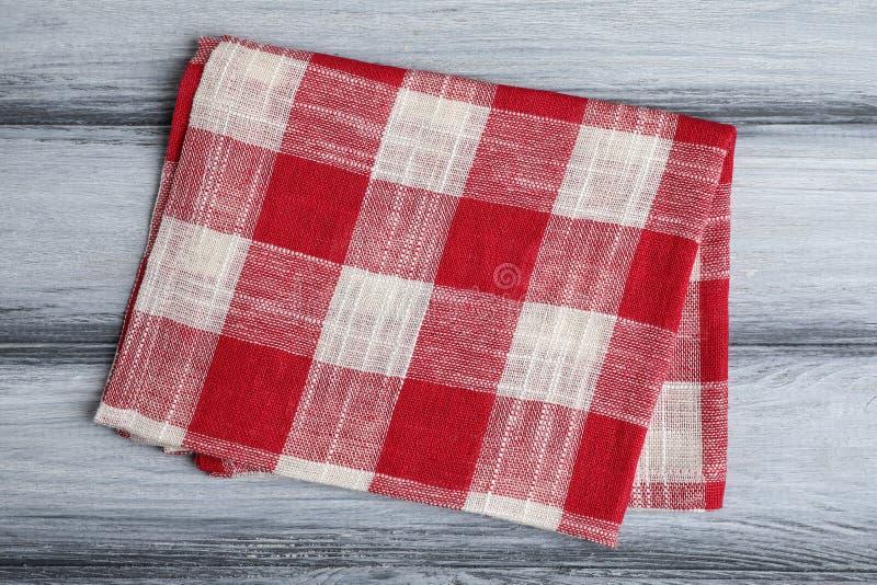 在木背景的红色格子花呢披肩洗碗布,顶面 免版税库存图片